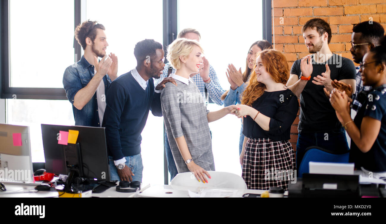 co-workers are congratulating new employee who has done work experience successfully - Stock Image