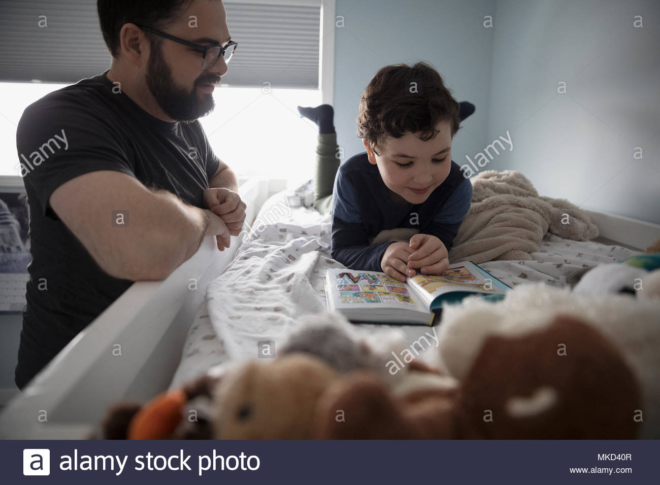 Father and son reading bedtime story on bunk bed - Stock Image