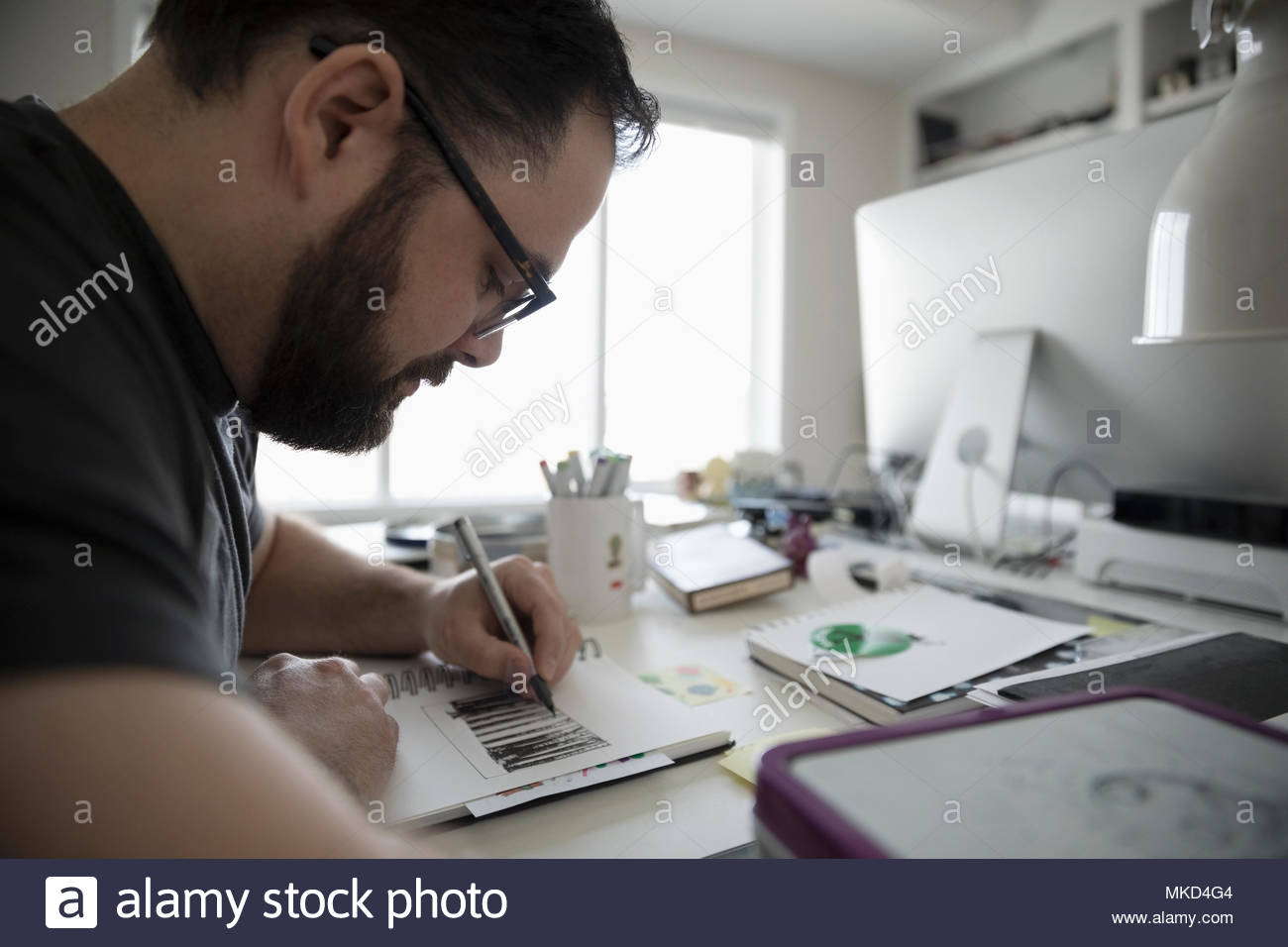 Focused male illustrator sketching in home office - Stock Image