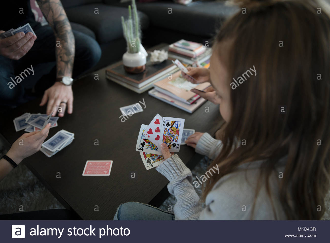 Girl playing card game with family - Stock Image