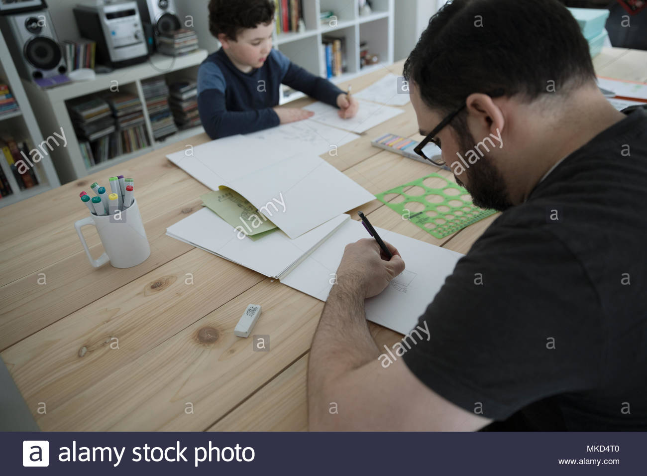 Father and son drawing at dining table Stock Photo