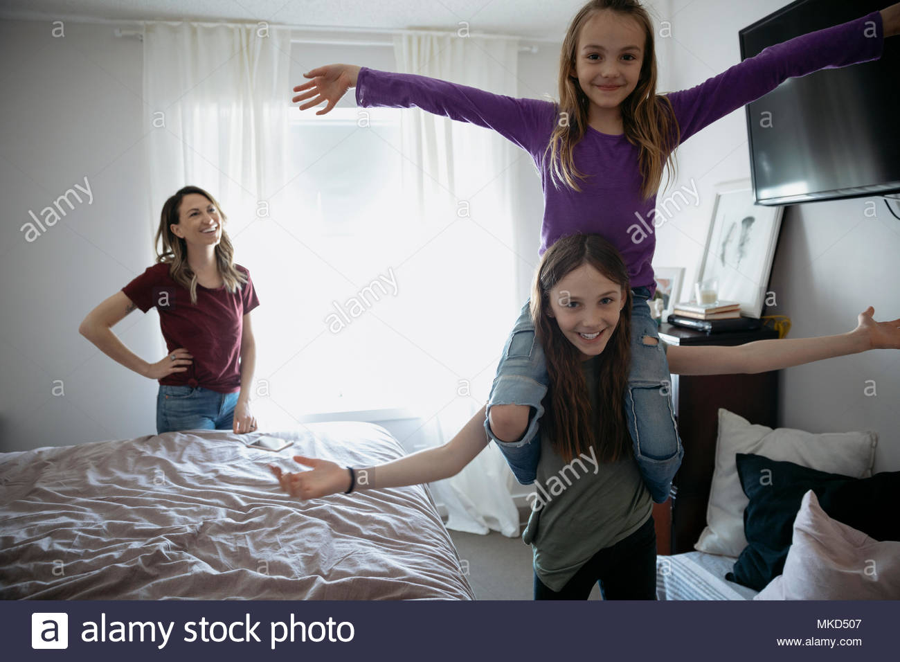 Portrait playful girl carrying sister on shoulders in bedroom - Stock Image