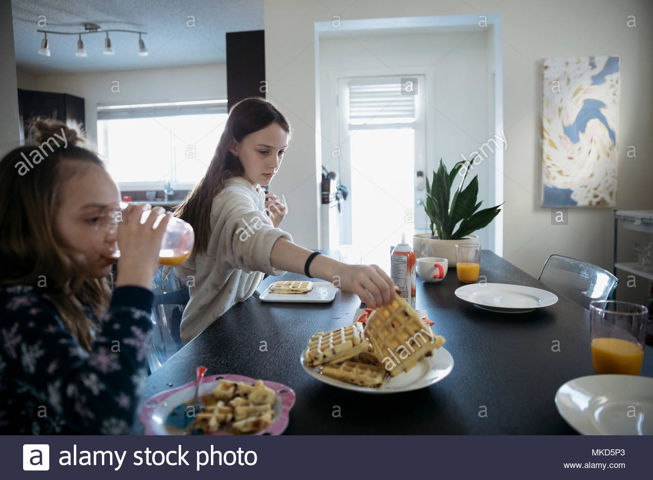 Girls eating waffles at dining table - Stock Image