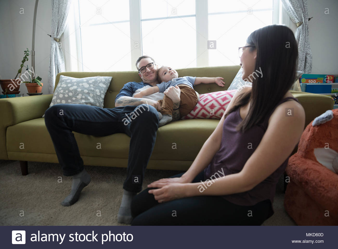 Young family relaxing in living room Stock Photo