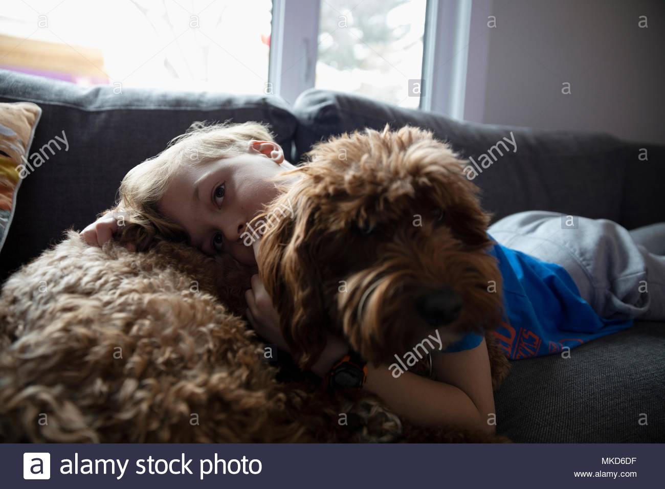 Portrait affectionate boy cuddling cute dog on living room sofa - Stock Image