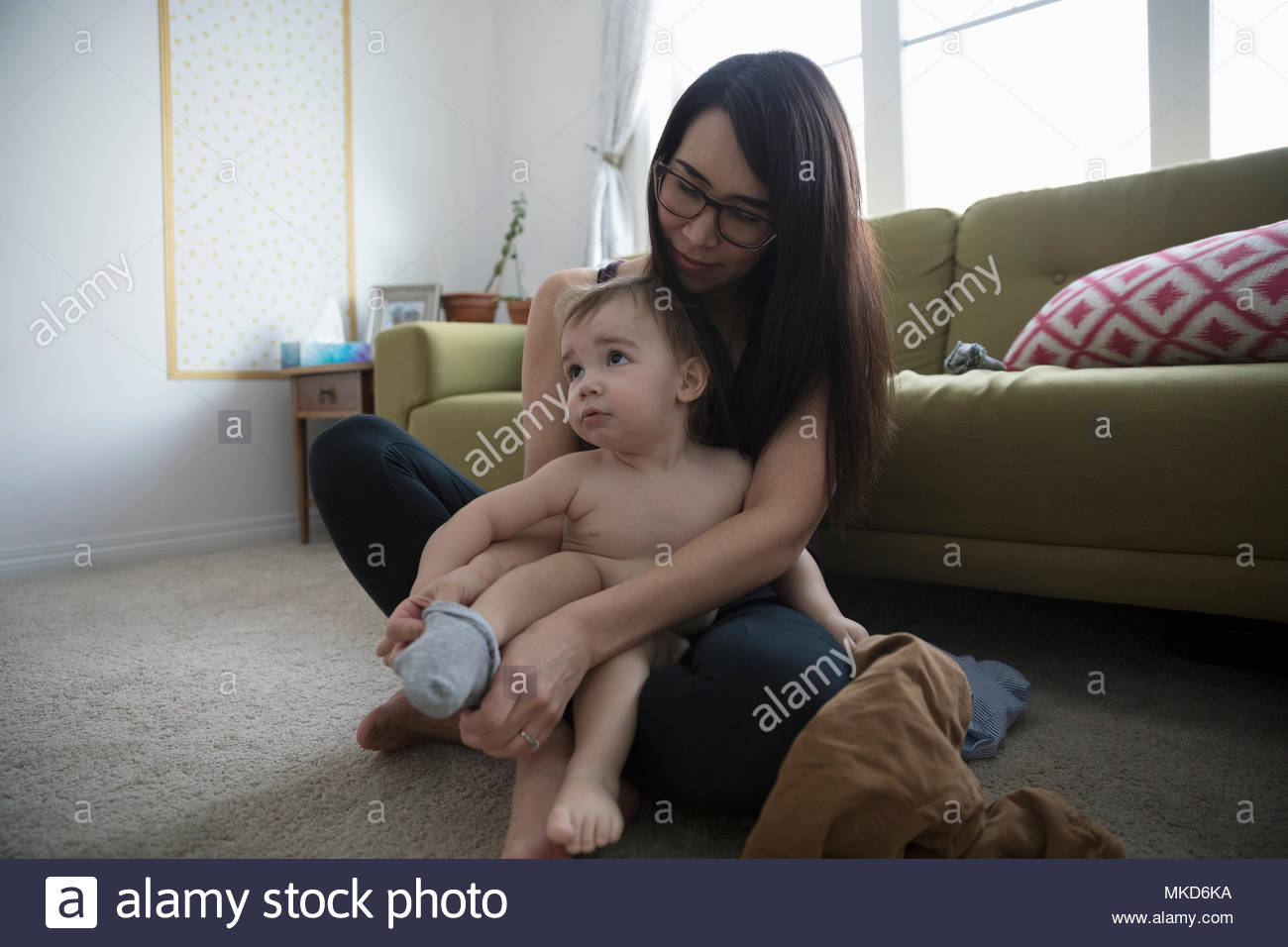 Mother dressing, putting socks on baby son - Stock Image