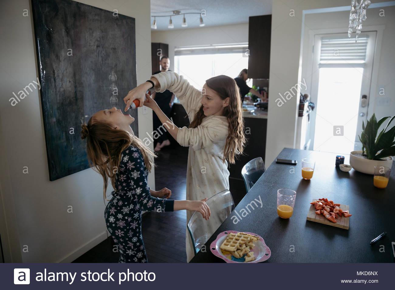 Playful sisters in pajamas enjoying spray whip cream at dining table - Stock Image