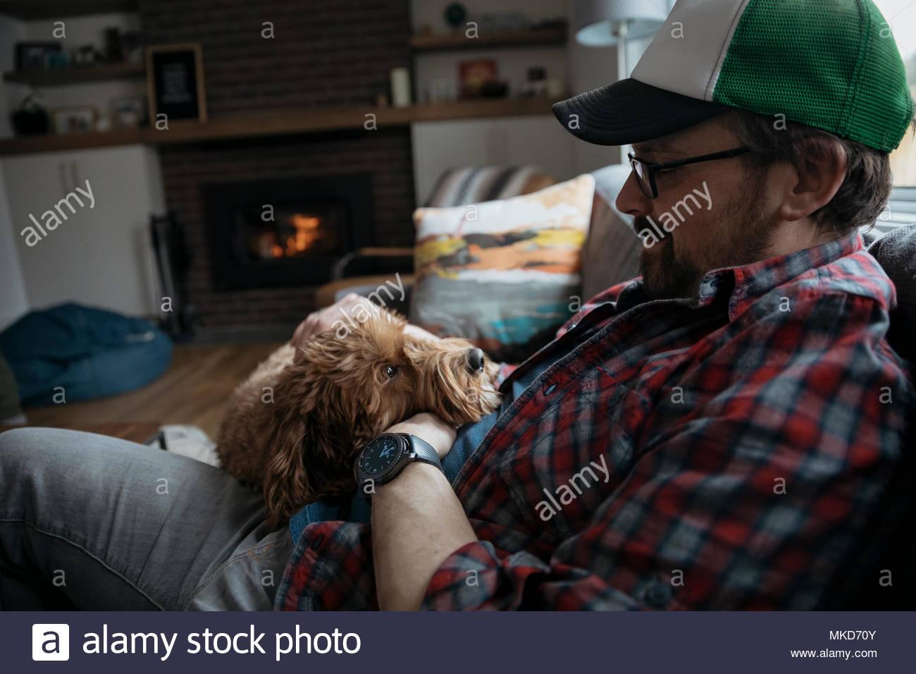 Man petting cute dog on living room sofa - Stock Image
