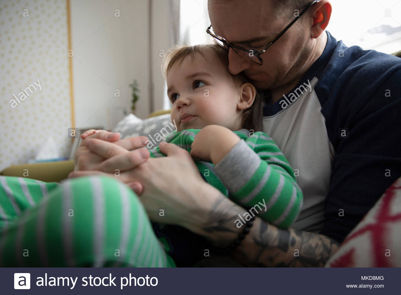 Affectionate, tender father cuddling baby son - Stock Image