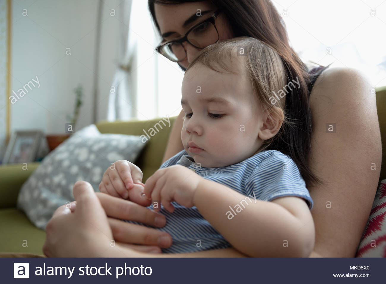 Mother holding curious baby son - Stock Image