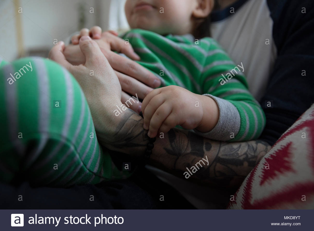 Close up affectionate, tender father cuddling baby son - Stock Image