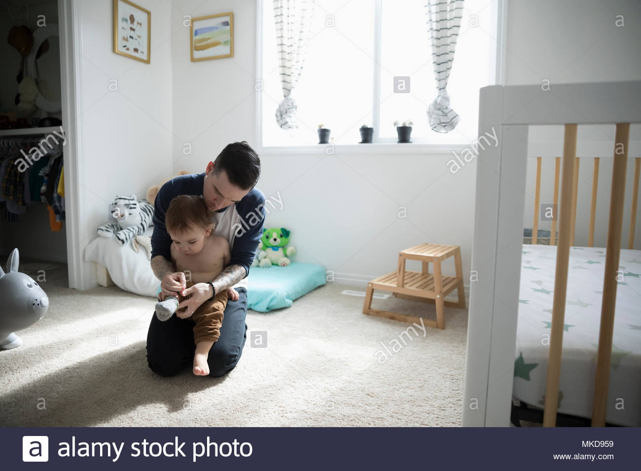 Father dressing, putting socks on baby son in nursery - Stock Image
