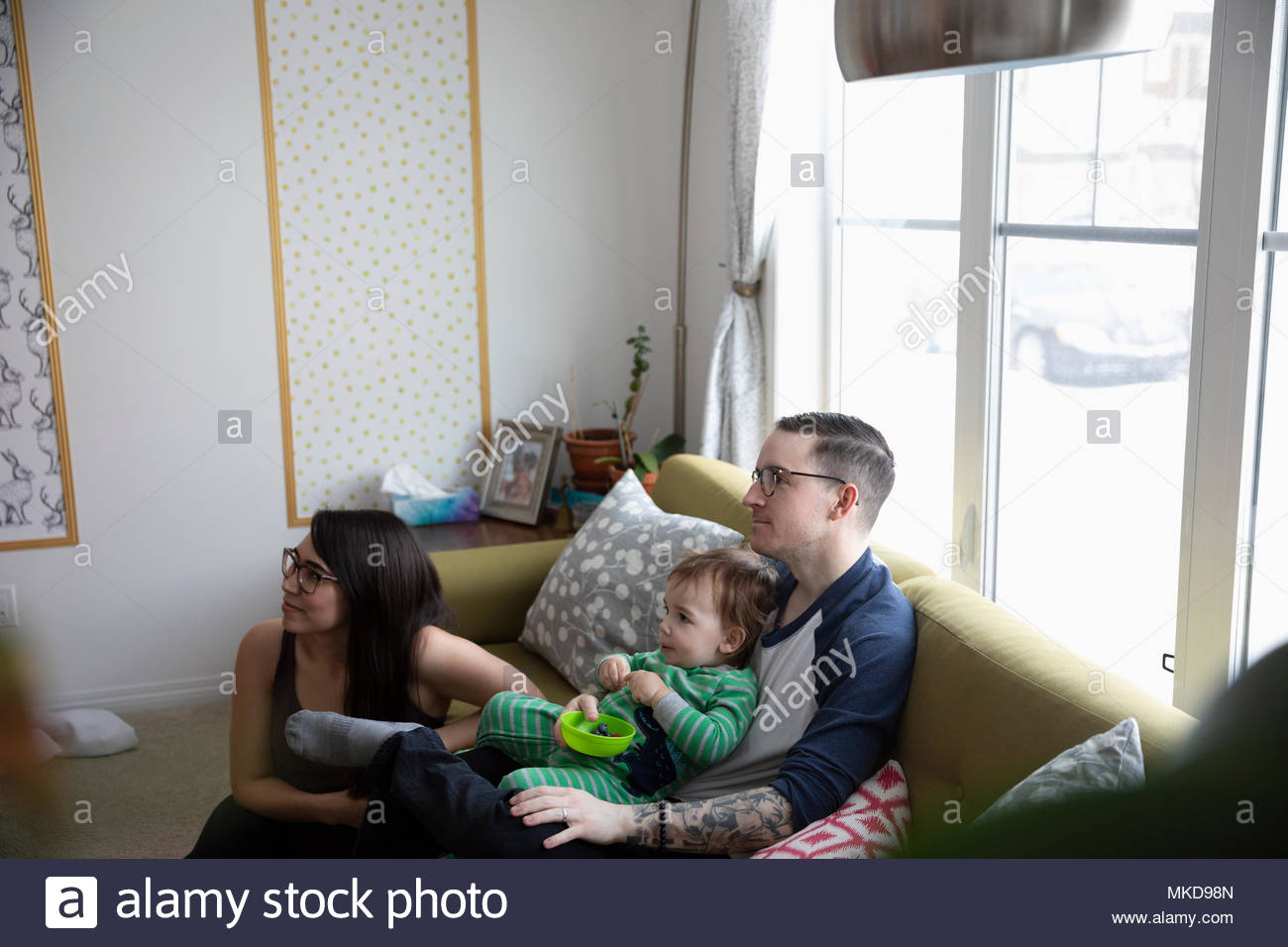 Young family eating, watching TV on living room sofa - Stock Image