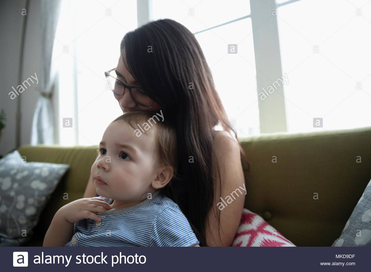 Affectionate, tender mother holding baby son on sofa - Stock Image