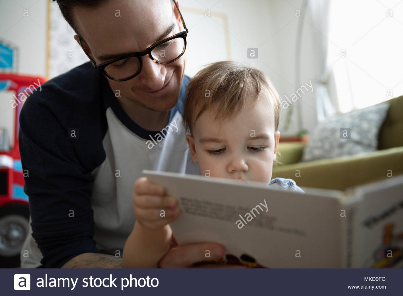 Father reading story book to baby son - Stock Image