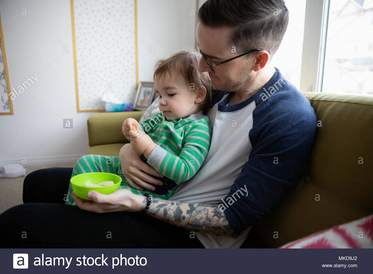 Father feeding baby son on sofa - Stock Image