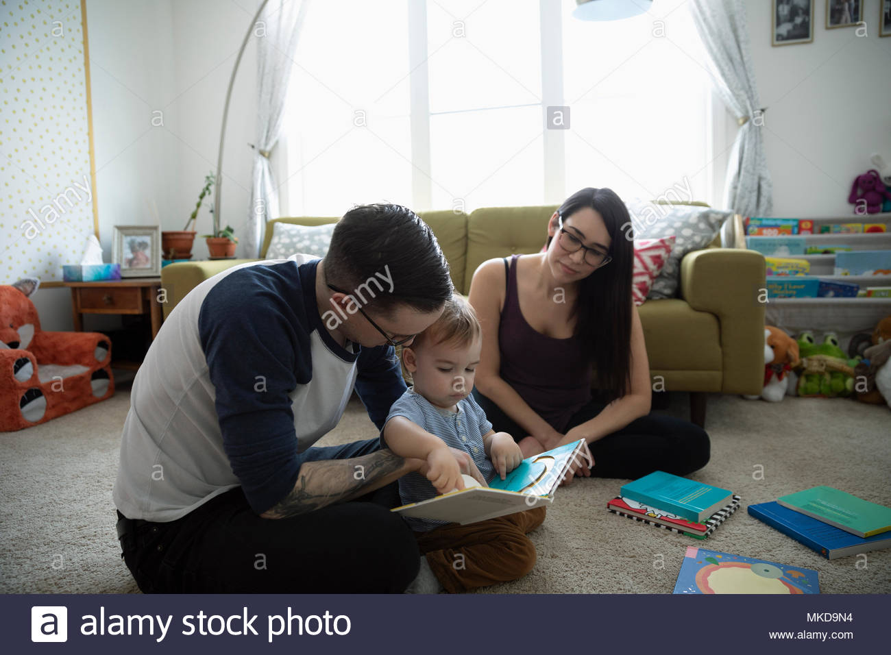 Parents reading story book to baby son in living room - Stock Image