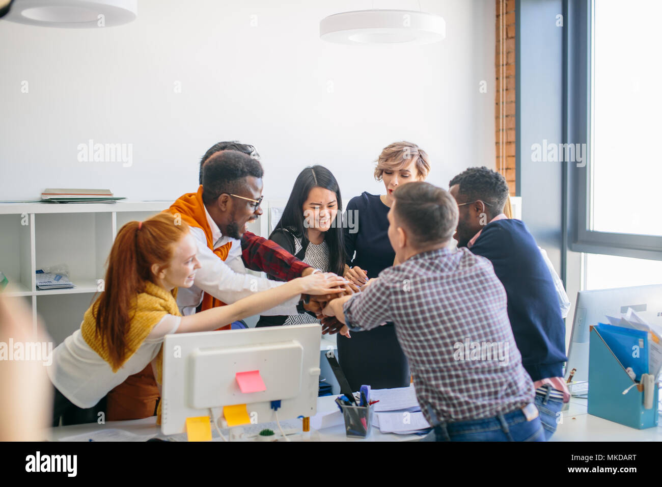 international group of students putting hands on the top of each other. close-up image - Stock Image