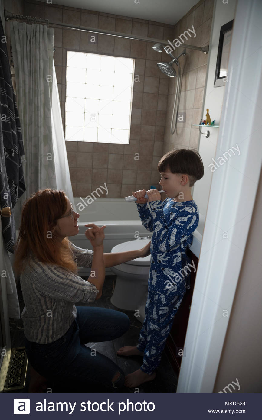 Mother guiding son brushing teeth in bathroom - Stock Image
