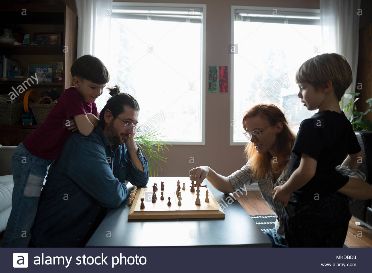 Family playing chess at living room coffee table - Stock Image