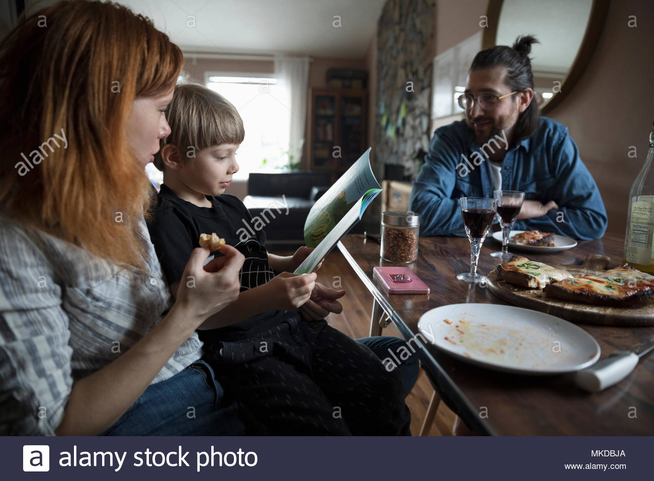 Family eating homemade pizza, reading book and drinking wine at dining table - Stock Image