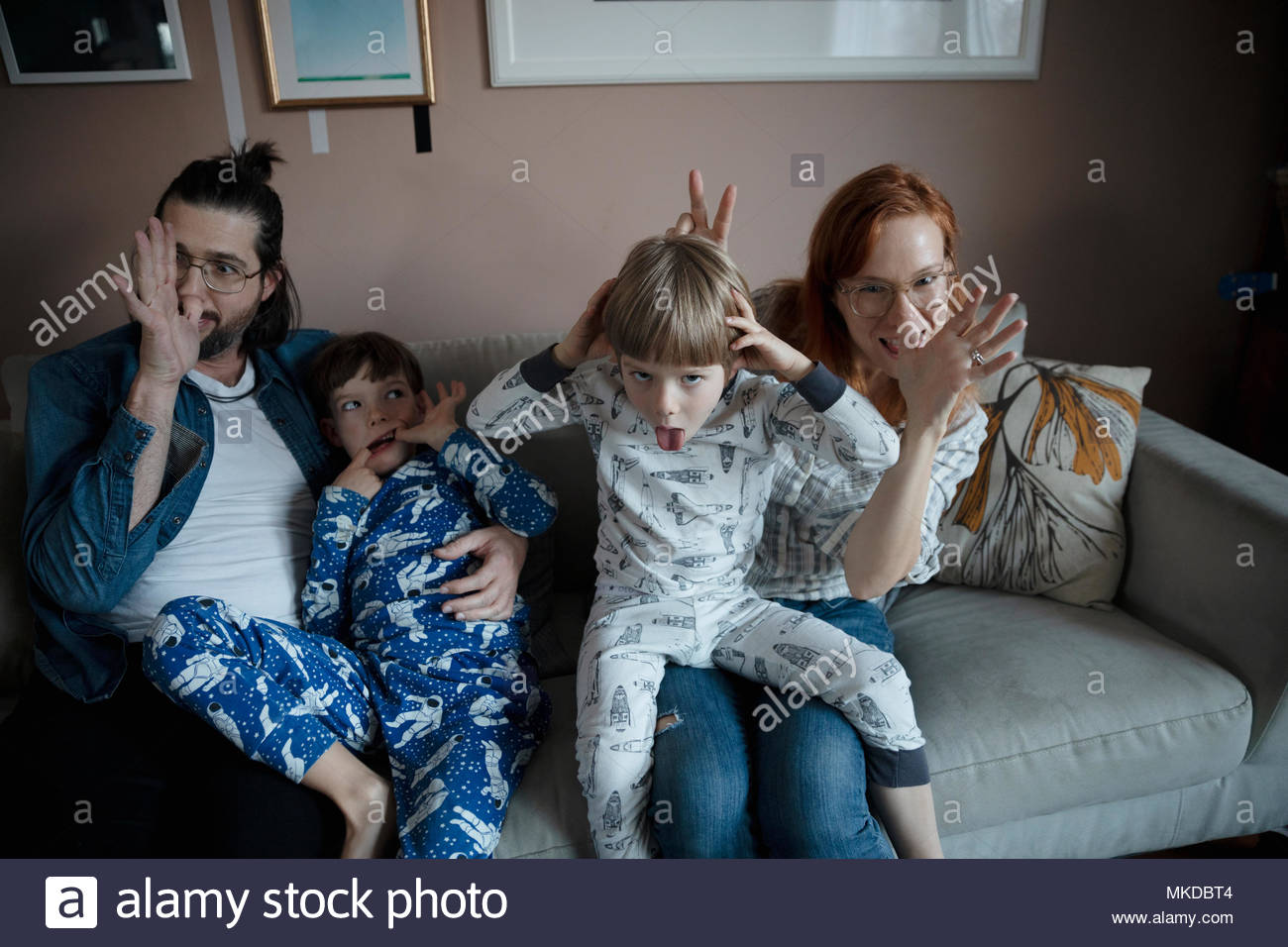 Portrait playful family making faces, gesturing on living room sofa - Stock Image