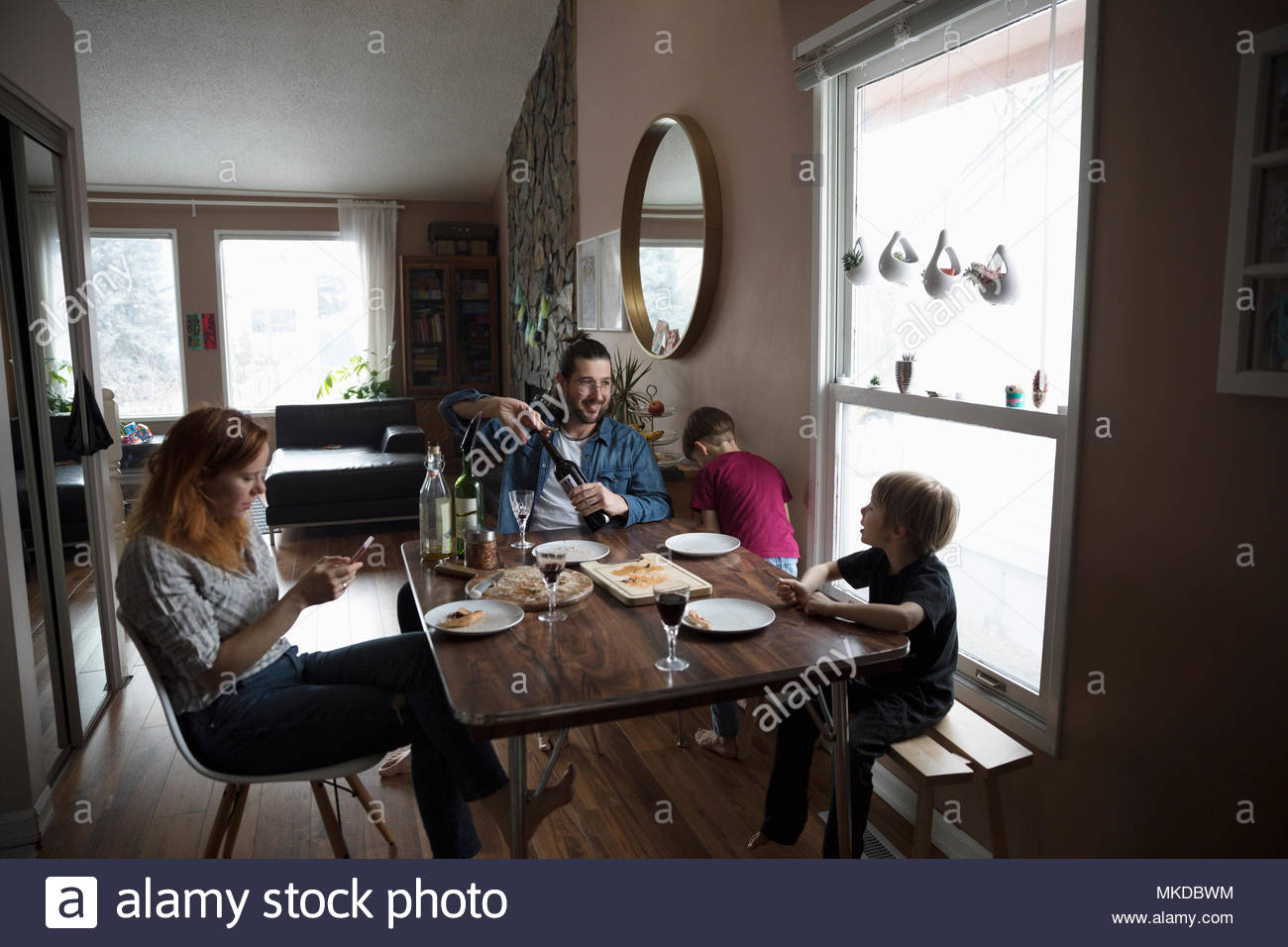 Family eating pizza at dining table - Stock Image