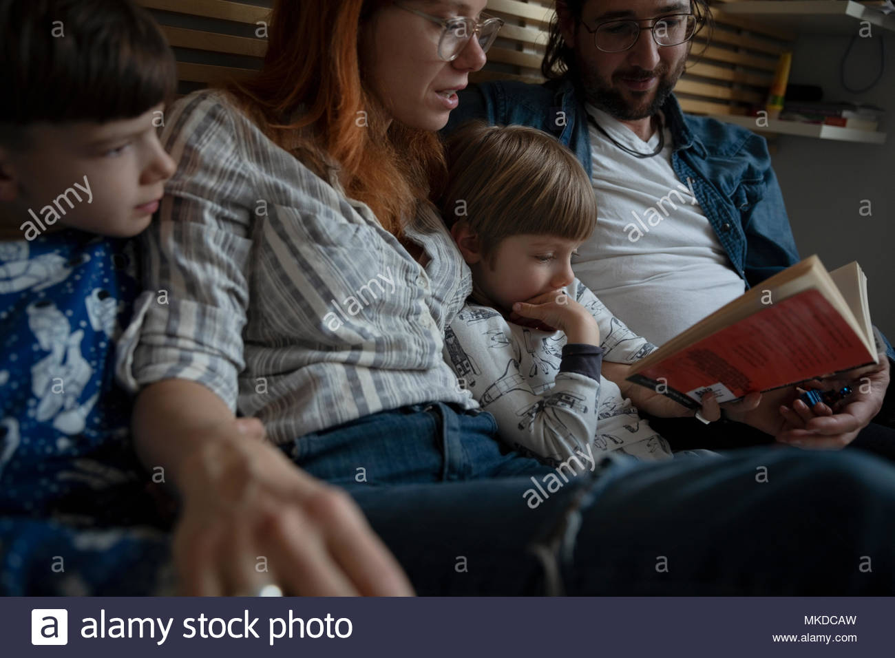Family reading bedtime story book - Stock Image