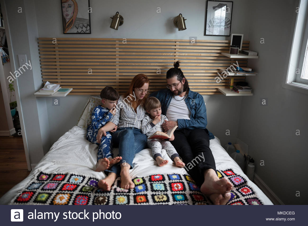 Family reading bedtime story book on bed - Stock Image