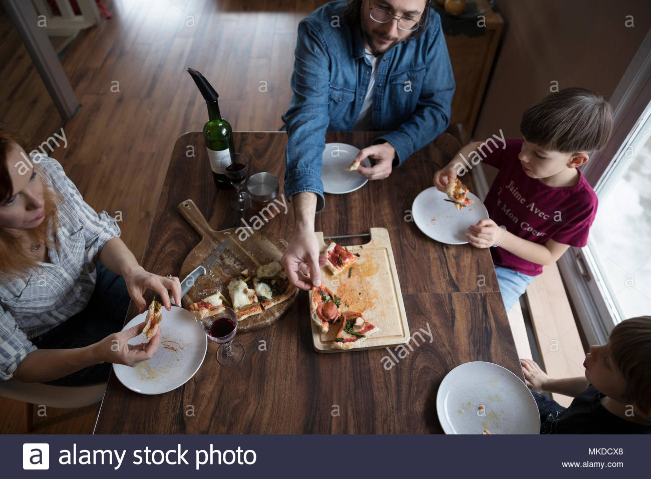 Overhead view family making homemade pizza at dining table - Stock Image
