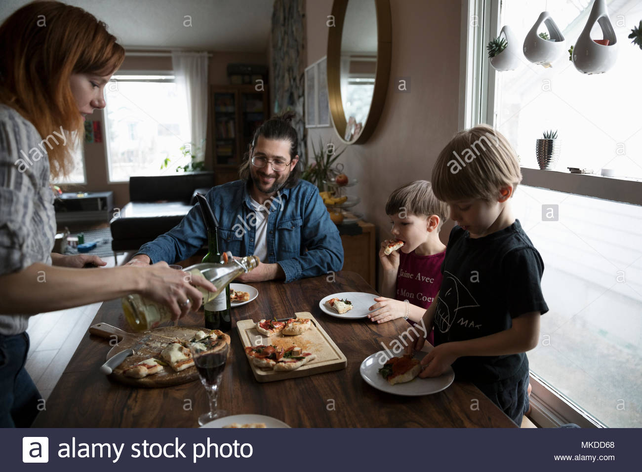 Family eating homemade pizza at dining table - Stock Image