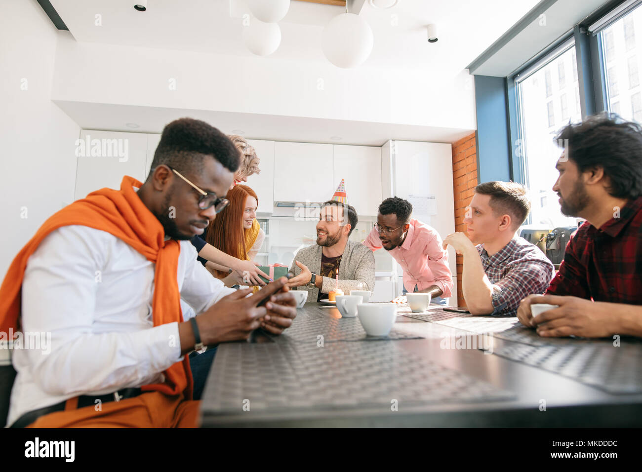 young african guy with mobile phone ignoring his co-workers birthday. introvert in the collective - Stock Image