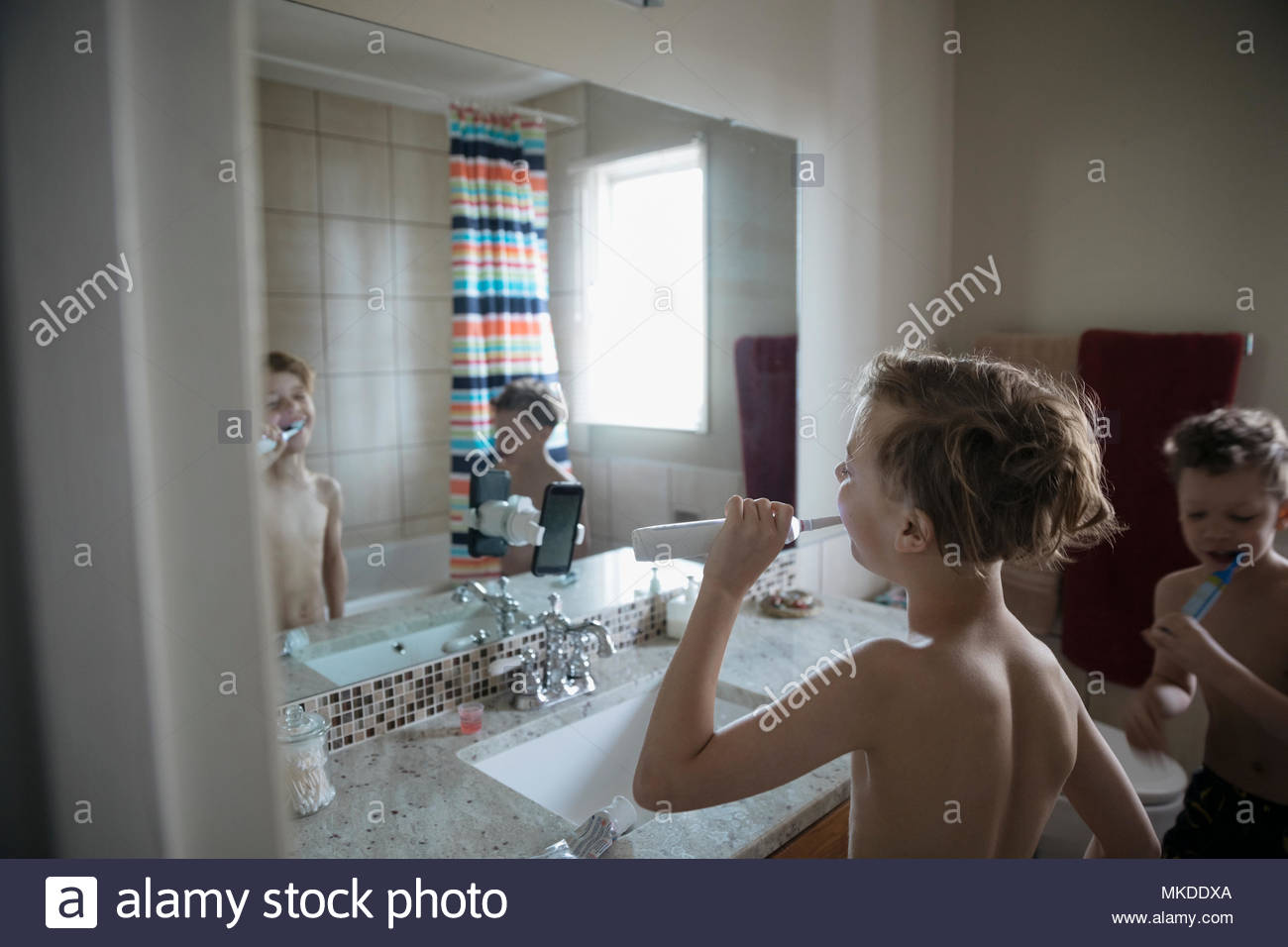 Bare chested boy brushing teeth in bathroom mirror - Stock Image