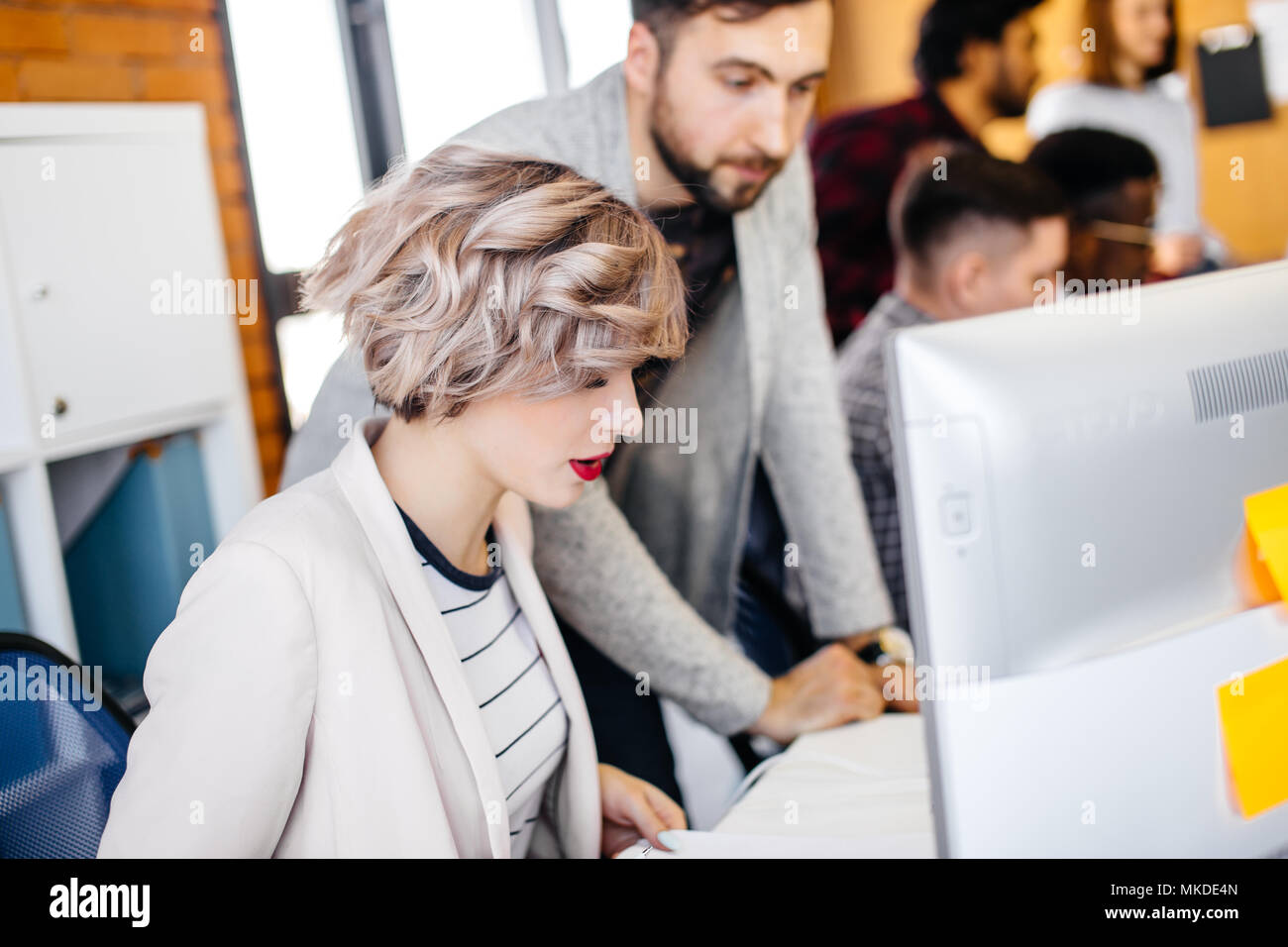 Startup good-looking business partners working together in loft office.close up photo of beautiful stylish secretary working with computer with blurre - Stock Image