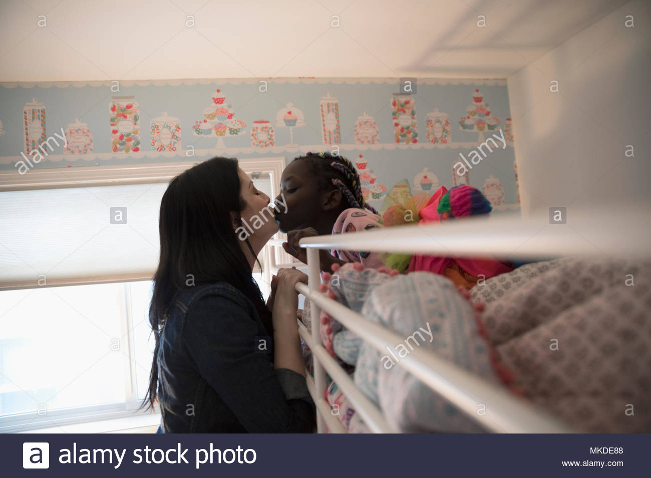 Affectionate mother kissing daughter waking in bunk bed - Stock Image
