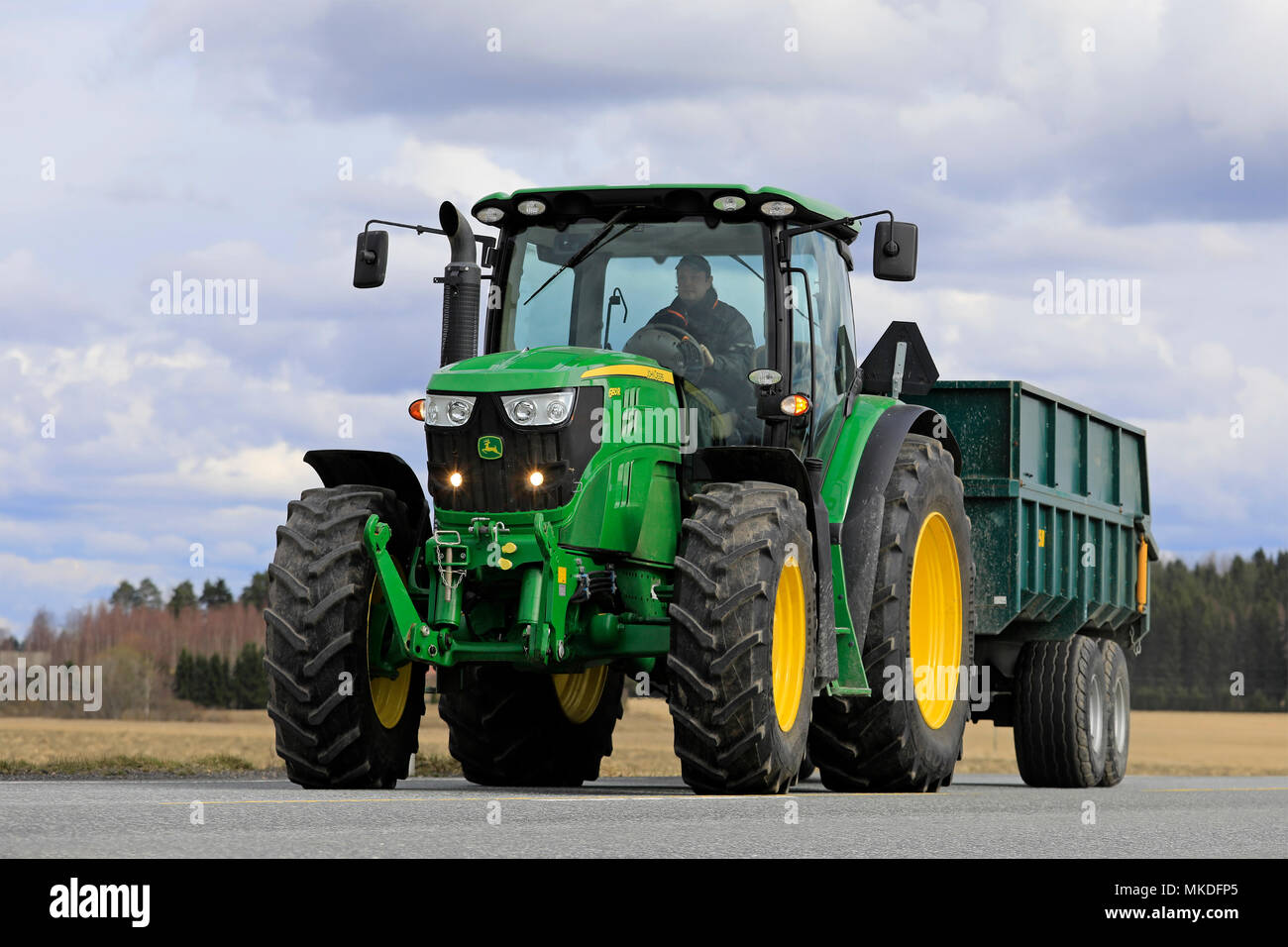 Farmer drives John Deere 6150R tractor and agricultural trailer on road. In 2018, late spring delays seeding. Jokioinen, Finland - April 30, 2018. Stock Photo