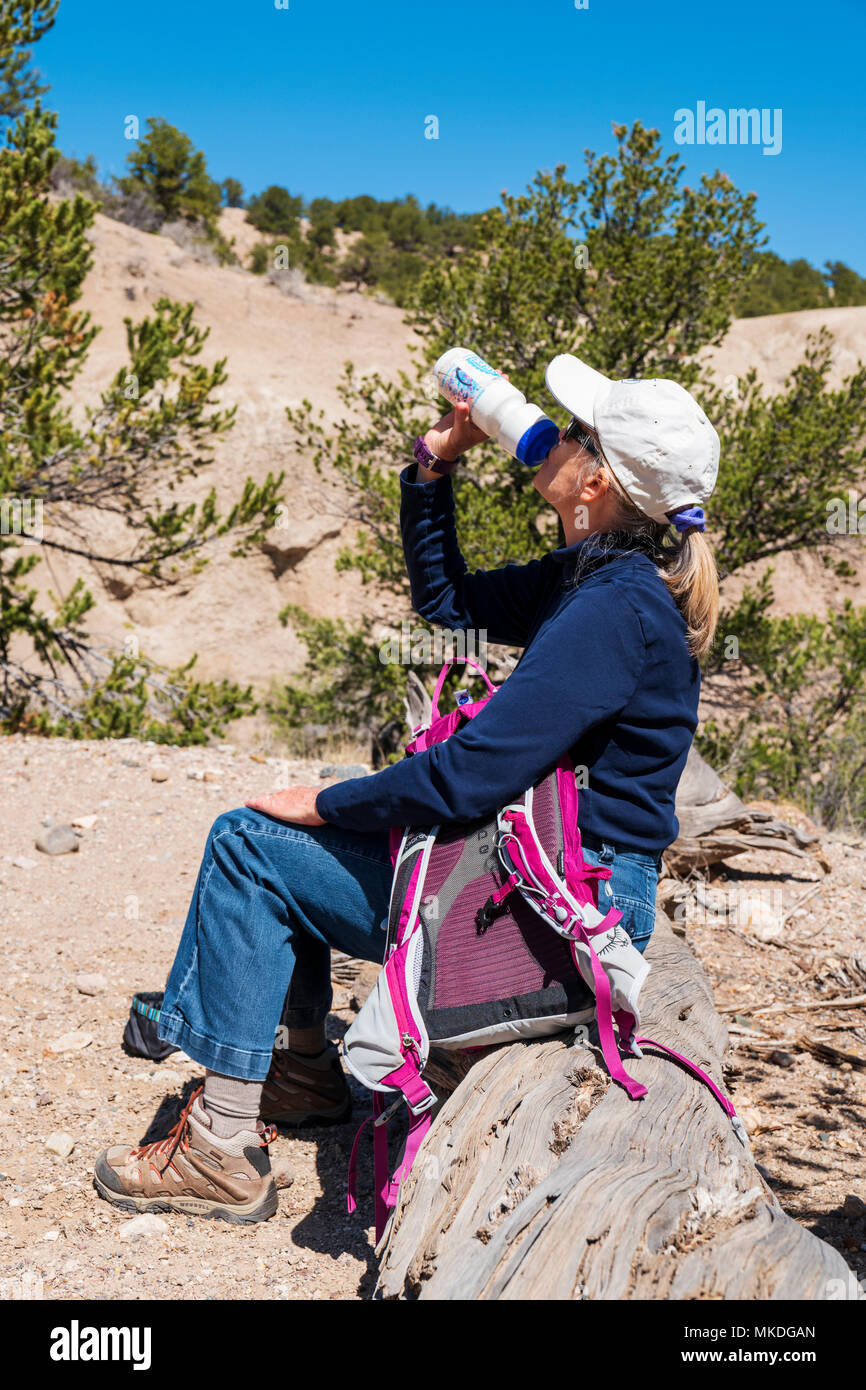 Female middle aged hiker pauses for a drink - Stock Image