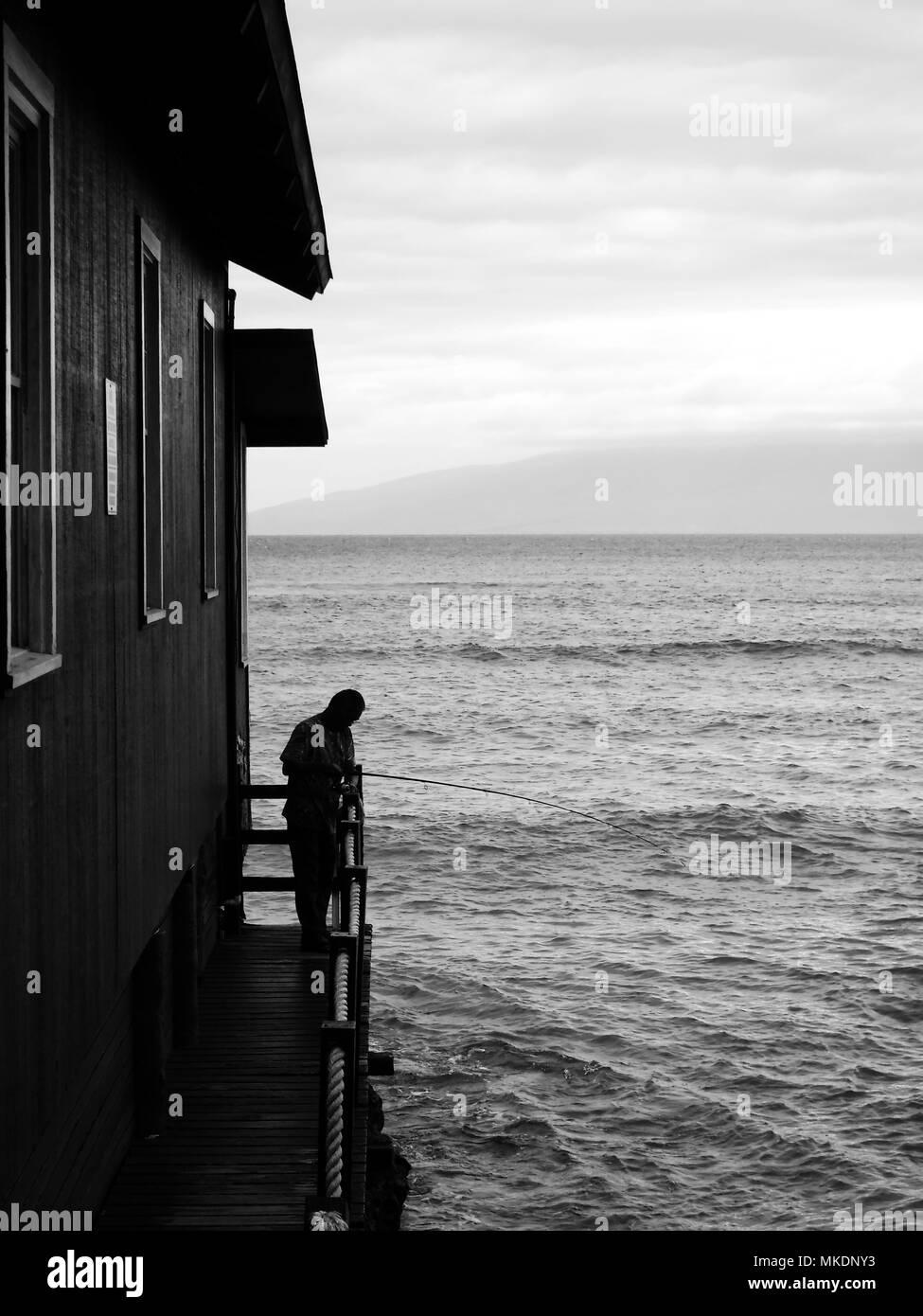 Man fishing next to building - Stock Image