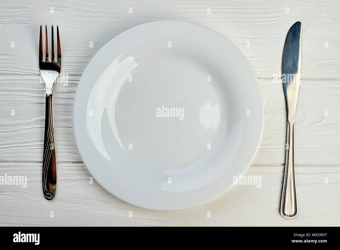Empty plate, fork and knife. Kitchen utensil on white wooden table ...