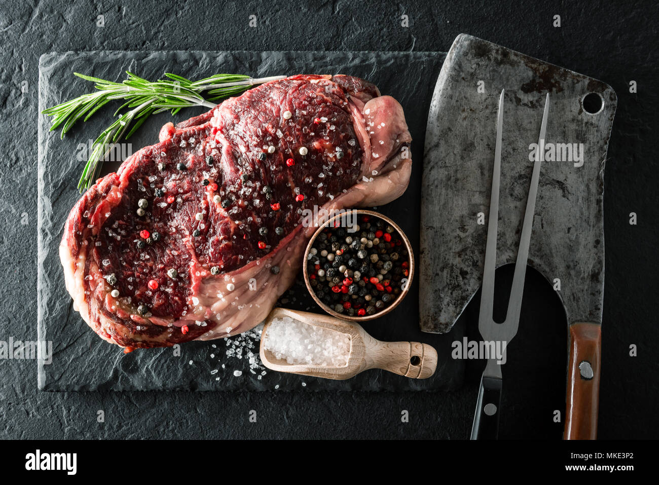 Marbling ribeye steak on black plate - Stock Image