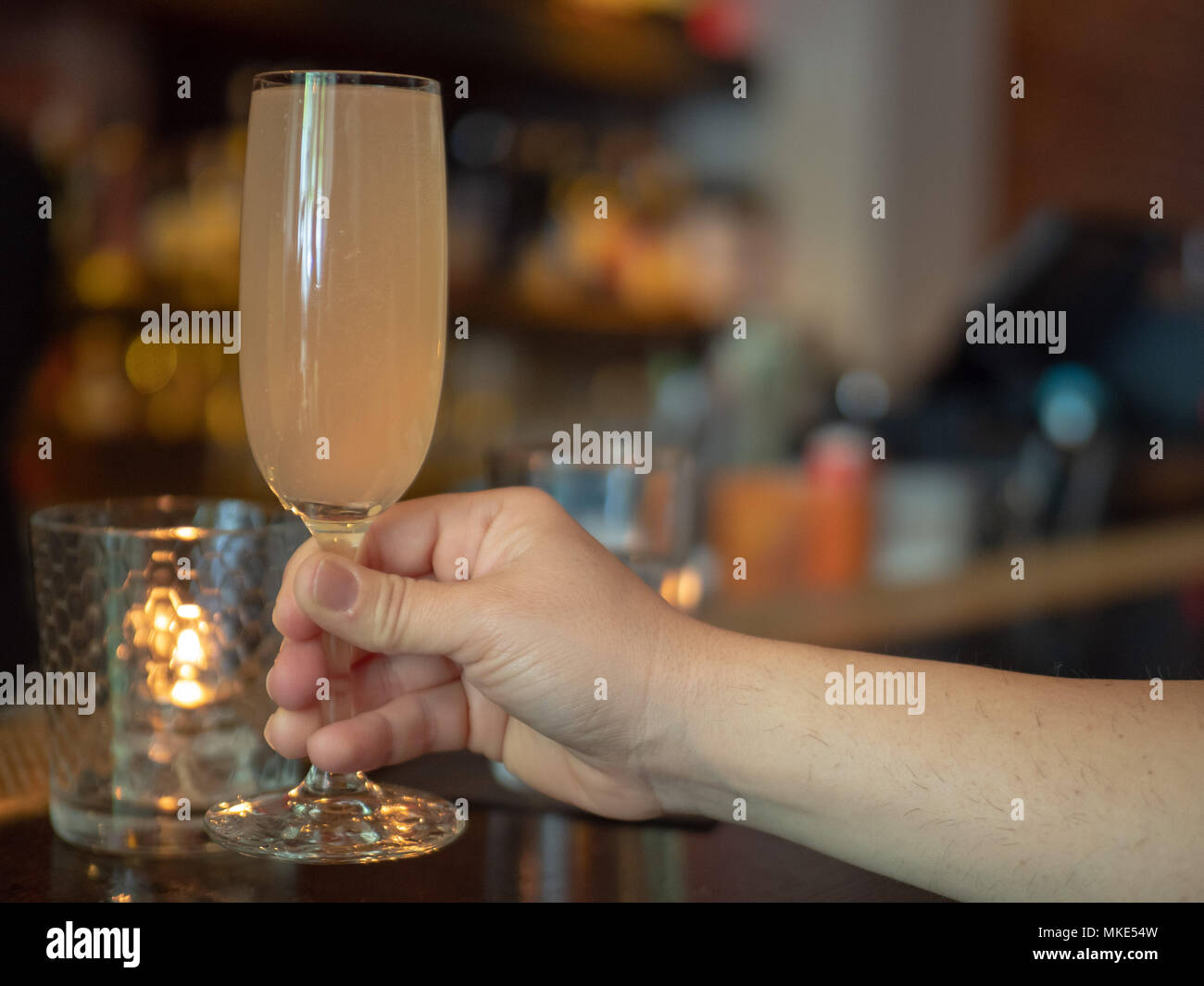 Woman lifting a wineglass filled with mimosa drink during