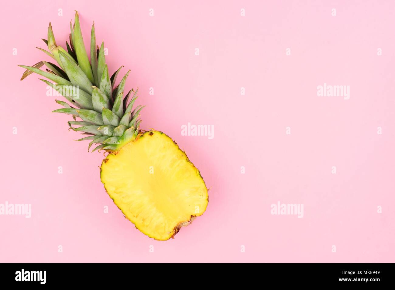 Half cut juicy pineapple on a pastel pink background. Minimal summer concept. Stock Photo