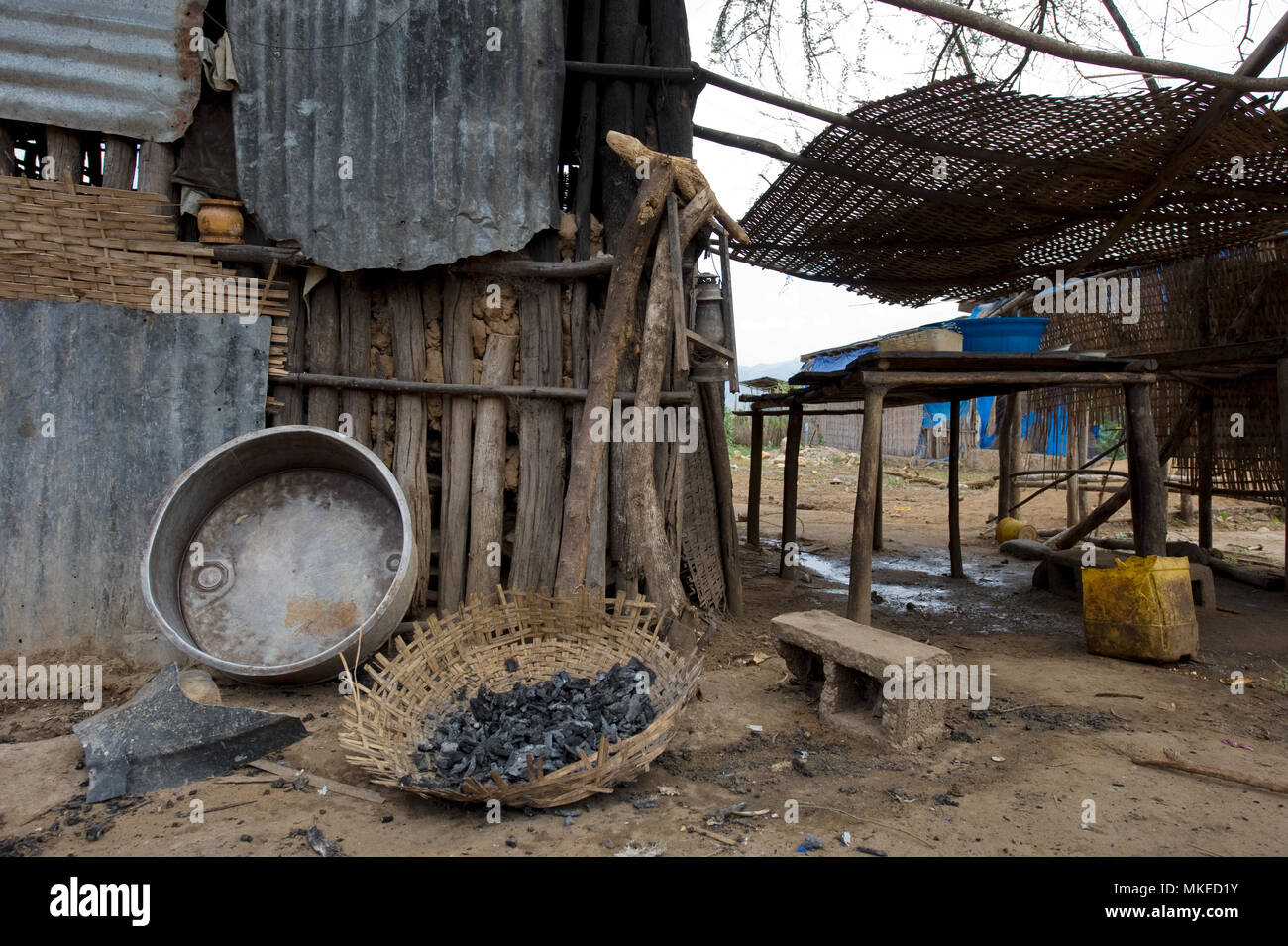 Yard Ethiopian village house, hedge of wooden sticks, awnings, scattered basins, cans, trash. - Stock Image