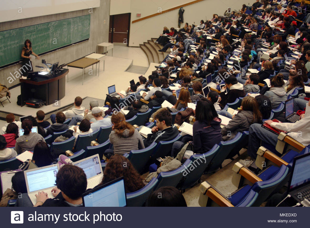 Students listen to a Proffessor teaching in a university lecture hall. - Stock Image