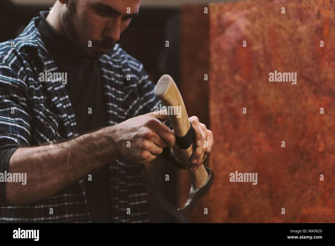 Man working in carpentry workshop. He wraps wooden handle of ax with leatherwork material. Men at work. Hand work. - Stock Image