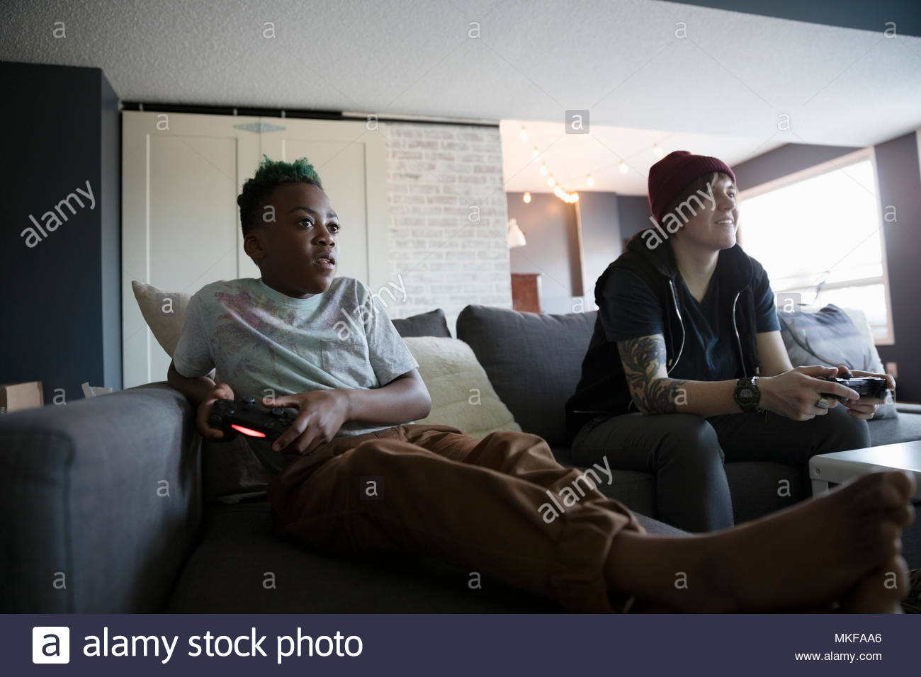 Babysitter and boy playing video game on sofa - Stock Image