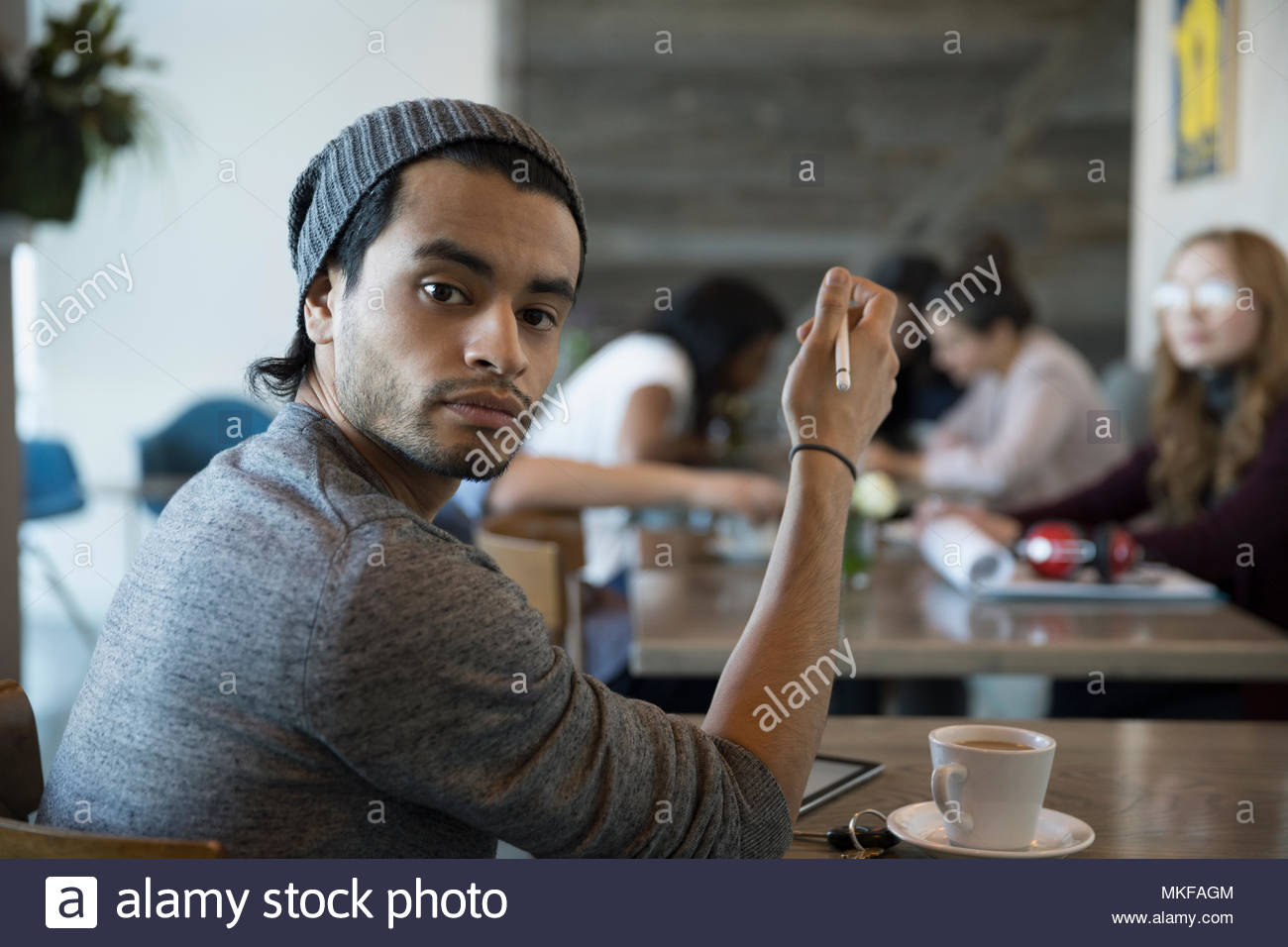 Portrait confident, creative young man with stylus using digital tablet in cafe - Stock Image