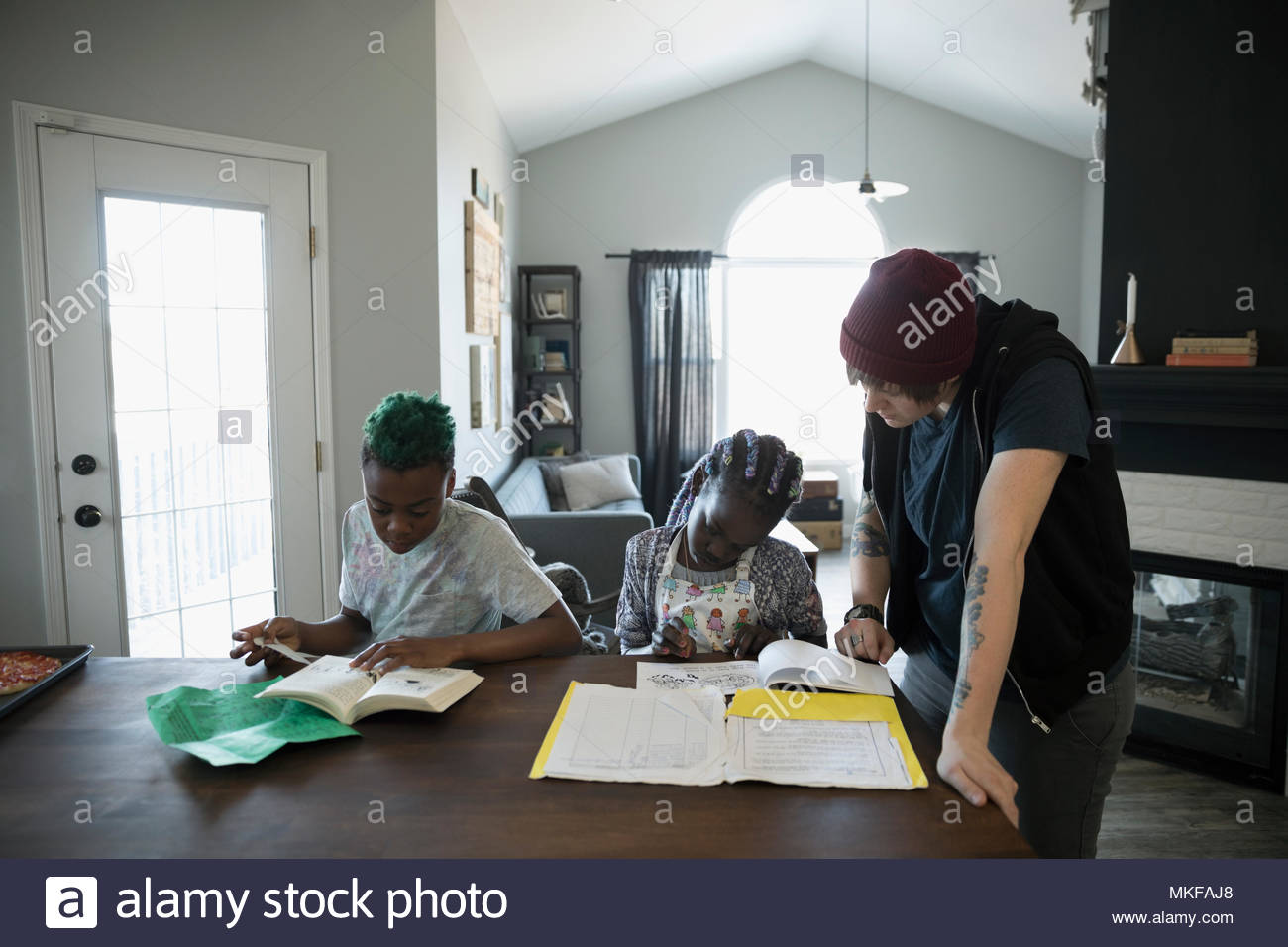 Tutor helping brother and sister with homework at dining table - Stock Image