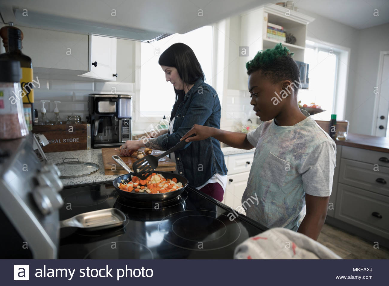Mother and son preparing and cooking vegetables at kitchen stove - Stock Image
