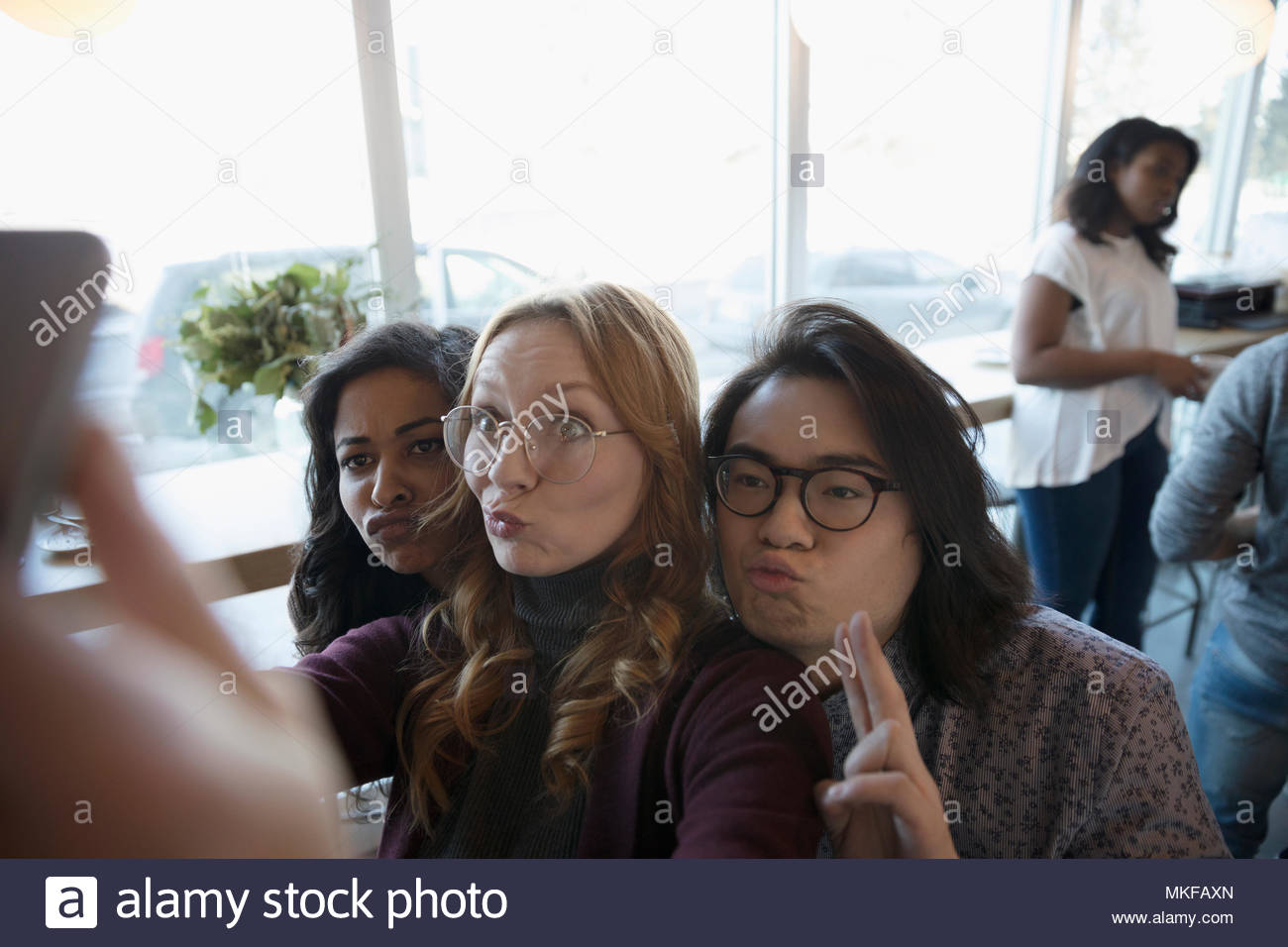 Playful, silly young friends making a face, posing for selfie - Stock Image
